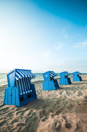 Four blue wooden beach chairs on sandy beach in the morning sun; Furnitures for the beach; Beach vacation; Relaxation by the sea