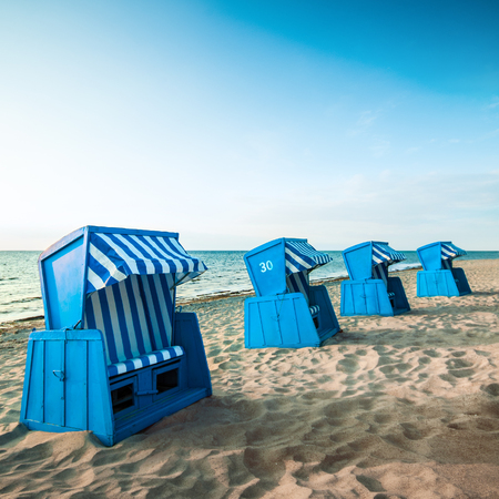 Four blue beach chairs in a line on sandy beach against cloudless sky; Blue wooden furnitures with blue-white cover by the sea shore; Beach vacation