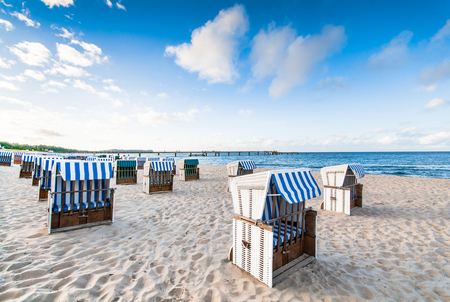 Sandy beach on the Baltic coast with locked beach chairs in the early morning; Beach furnitures in the sand; White, roofed wicker chairs with blue-white cover; Maritime scenery Standard-Bild