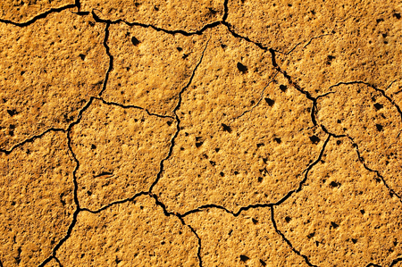 Light brown, dried out and cracked soil - top view; Result of severe drought; Water shortage; Ocher colored cracked ground for background or texture