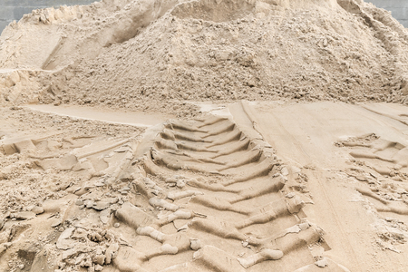Sand - construction material for road construction or buildings; Tracks of construction vehicle in fine sand in landscape format