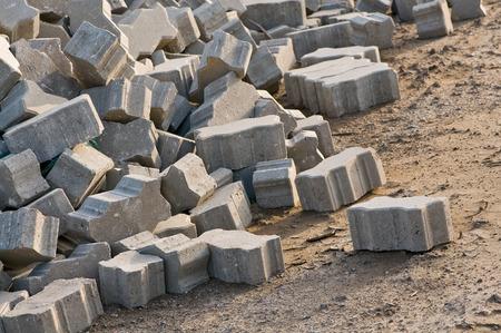 Heap of stones for interlocking paving; Interlock concrete products; Building material on construction site Standard-Bild