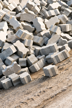 Light gray interlocking paving stones piled on construction site - upright format; Building material for pavings; Concrete products