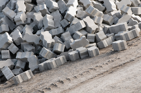 Heap of gray paving stones on construction site in sunlight - landscape format; Interlocking paving stones; Concrete products for paving works Standard-Bild