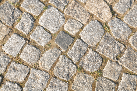 Pavement with gray cobblestones closeup - top view, for background or texture; Paved surface