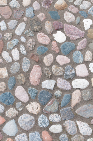 Pebble stone pavement in top view for background or texture; Pebble stones in different sizes and shapes laid out in sand; Ornamental stone paving;