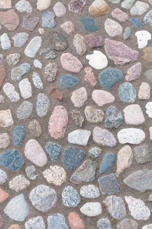 Kieselsteinpflaster in der Draufsicht für Hintergrund oder Beschaffenheit; In Sand gelegte Kieselsteine in verschiedenen Größen und Formen; Ziersteinpflaster;