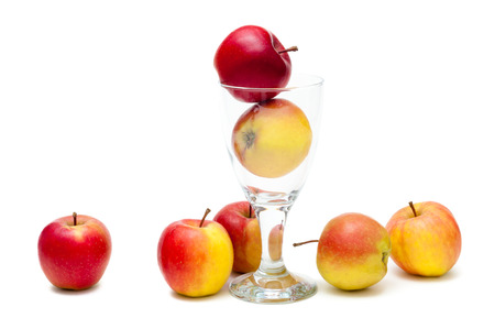 Red and yellow ripe apples on white ground and in decorative glass against white background; One apple a day; Crispy and juicy round fruit