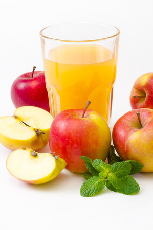 Glass with apple juice, whole apples and halved apple decorated with mint sprig against white background; Delicious and healthy energy source