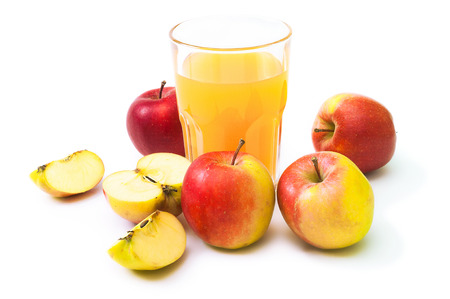 Red-yellow apples, whole and halved, and a glass of naturally cloudy apple juice on white background; Crispy and juicy energy supplier; Ripe fruits; Healthy nutrition
