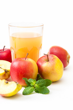 Glass of freshly sqeezed apple juice, whole apples and some apple slices, decorated with mint leaves on white background; Refreshing natural beverage - rich in vitamins; Ripe, yellow-red fruits Standard-Bild