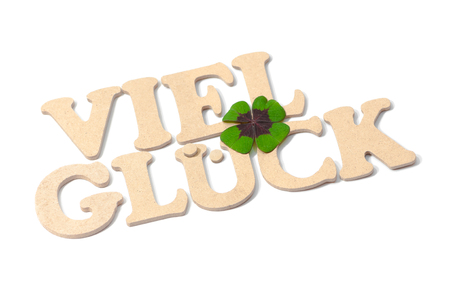 Good luck! Two words composed with wooden letters, decorated with four-leaf clover on white background; Greeting card; Congratulations Stock Photo