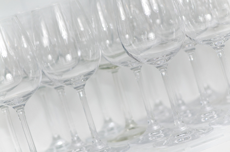 Wine glasses side by side in white shelf at gastronomy - closeup and in landscape format; Glassware; Catering sector