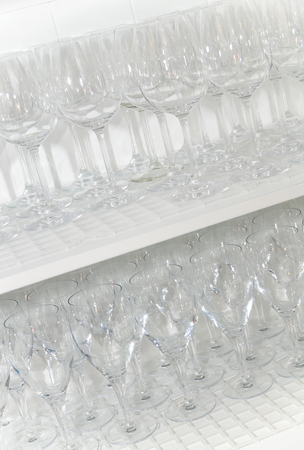 Stock photography different wine glasses on white shelf in closeup; Gastronomy; Equipment of catering trade; Empty glasses at a shelf