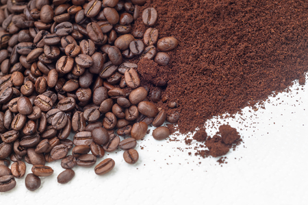 Roasted coffee beans and coffee on white surface in closeup; Coffee specialties; Processed coffee beans Imagens