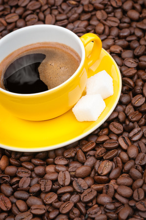 Brown cup with black coffee on dark brown, roasted coffee beans; Coffee break; Popular and stimulating hot beverage; Coffee indulgence