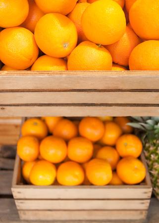 Ripe oranges in wooden fruit boxes; Offer in fruit market; Orange citrus fruits