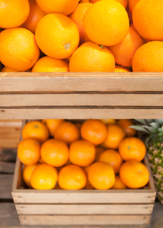 Ripe oranges in wooden fruit boxes; Offer in fruit market; Orange citrus fruits Standard-Bild - 100617533