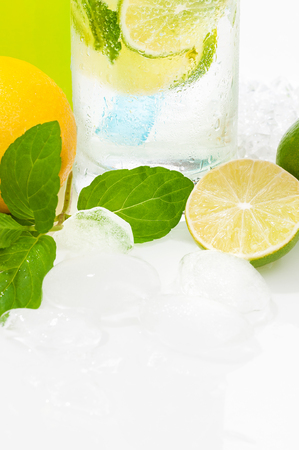 Refreshing icy cold drink with mineral water, lime slices and mint leaves; Glass of water decorated with ice cubes, lemon and lime and mint leaves; Low-calorie beverage