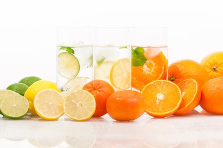 Refreshing cold beverages - low in calories; Three glasses of mineral and citrus fruits on white background; Healthy thirst quencher