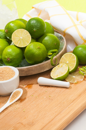 Fresh green limes - whole fruits and slices and brown sugar on wooden chopping board; Preparation of sweet and sour cocktail; Citrus fruits Standard-Bild