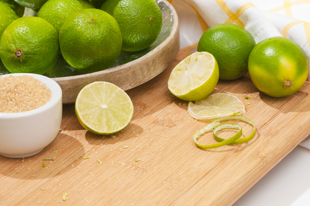 Green limes on wooden chopping board; Aromatic citrus fruits - fresh ingredient for drinks or cocktails; Brown sugar and limes in white porcelain dishes Standard-Bild