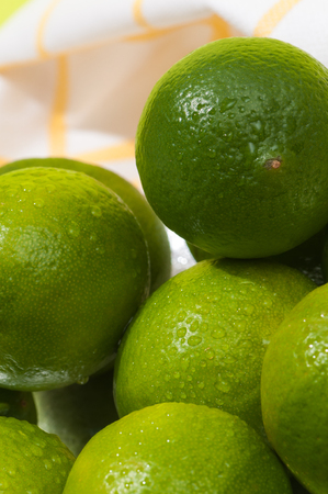 Green limes in closeup; Green citrus fruits on kitchen towel; Sour fruits; Ingredient for cocktails