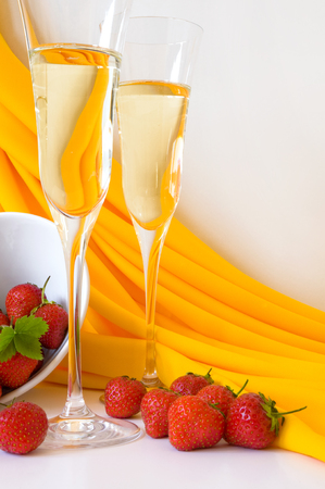Two glasses of sparkling wine offered with ripe red strawberries; Elegant glasses and white dish with yellow summer drapes against white background Standard-Bild