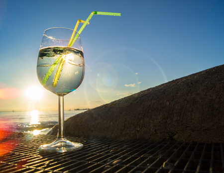 Cooled cocktail in glass with drinking straws against sunset over the water; Refreshing drink at the end of a sunny summer day; Hugo cocktail