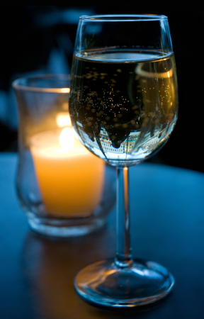 A glass of white wine on a table in the evening light; Stimulating beverage; Indulgence at the end of work; Alcoholic beverage; Wine consumption