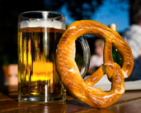 A glass of beer and a pretzel on a table in closeup; Hearty snack; Visit at beer garden in the evening; Alcoholic beverage and special bread Standard-Bild