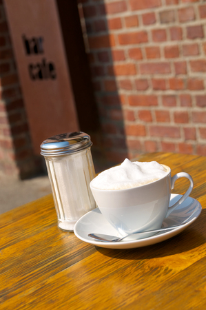 Coffee drink with milk foam served in white porcelain cup and sugar shaker on wooden table in sunlight; Coffee break Standard-Bild