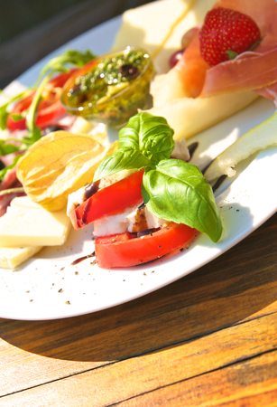 Hearty breakfast or light snack for inbetween - Italian style; White porcelain plate with tomato and morzarella cheese, melon and ham, green pesto and some fruits