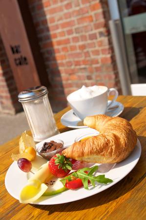 Small breakfast served on the sun terrace of cafe; Croissant, jam, hazelnut spread on white porcelain on wooden table in sunlight Standard-Bild