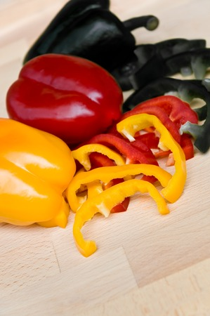 Black, red and yellow bell peppers on wooden ground - upright format; Sweet peppers - whole and in slices - in national colors of Germany or Belgium; Healthy snack for sports fans