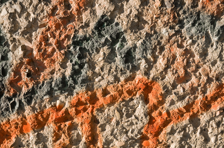 Concrete wall with grey and orange spray paint in closeup - landscape format; Graffity on rough concrete wall for background or texture; Damage to property with lacquer paint Standard-Bild