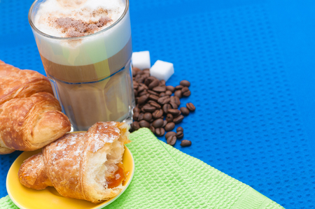 Small breakfast or snack with crispy croissant and a coffee drink; Coffee break with delicious pastry