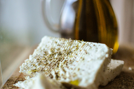 close up of feta cheese(Greek cheese) slices on a wooden serving board and a bottle of olive oil in nature light