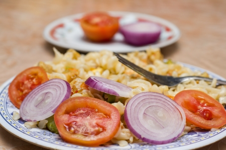 Macaroni with Onions and Sliced Tomatoes in background photo