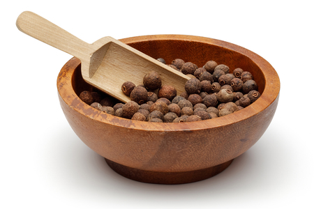Allspice berries in wooden bowl with scoop