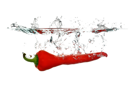 Red pepper dropped in water isolated on white background