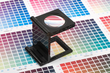 Printing loupe standing on colour swatch paper