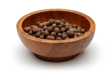 Allspice berries in wooden bowl with scoop isolated on white background