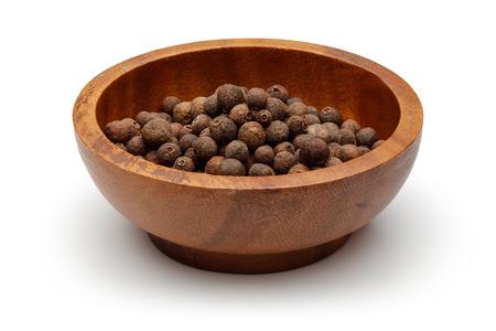 Baies de piment de la Jamaïque dans un bol en bois avec scoop isolé sur fond blanc