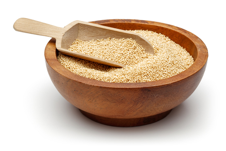 Amaranth grains in wooden bowl with spoon isolated on white background