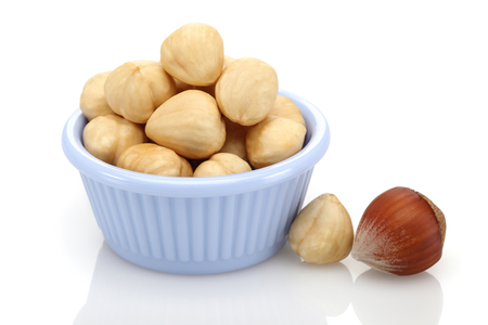 Hazelnuts in bowl isolated on white background