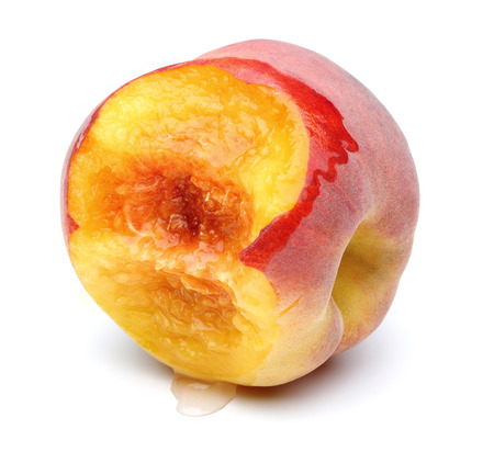 Bitten juicy peach isolated on white background Фото со стока