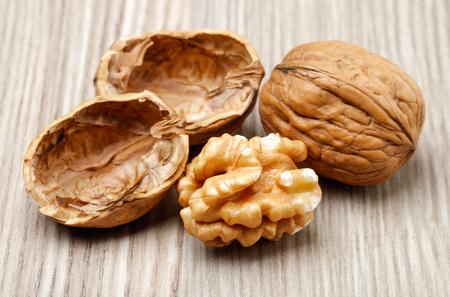 Hele en gebarsten walnoten op houten achtergrond