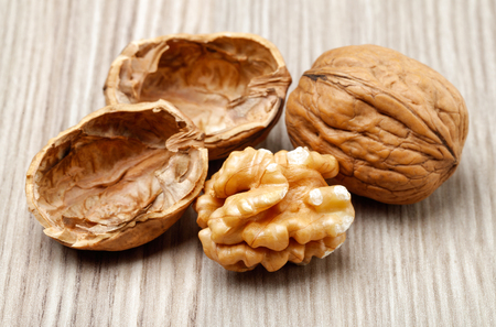 Whole and cracked walnuts on wooden background