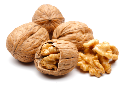 Whole and cracked walnuts isolated on white background